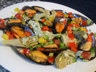 Presentación final de plato de mejillones con ensalada y alcachofas con vinafreta