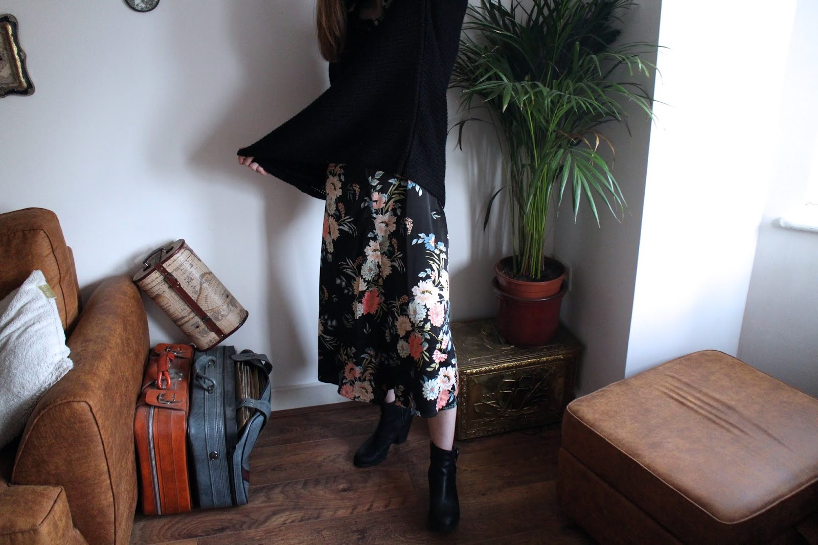 Vintage style room and crop of girl wearing floral maxi dress pulling black jumper