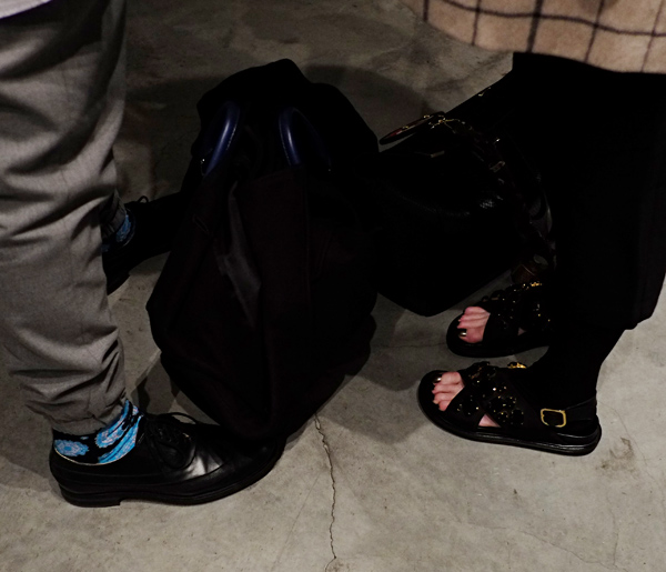 Black bags, him business lace up shoe, fun blue 'happy' socks. Her, unusual half sock open toe black bling sandals.. Street Fashion Sydney - Photographed by Kent Johnson.