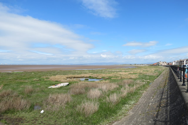 View across a strip of salt marsh from the promenade with Lake District fells on the horizon.