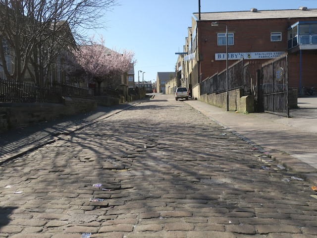 Cobbled street, industry, old housing, new housing, community centre, pink blossom.