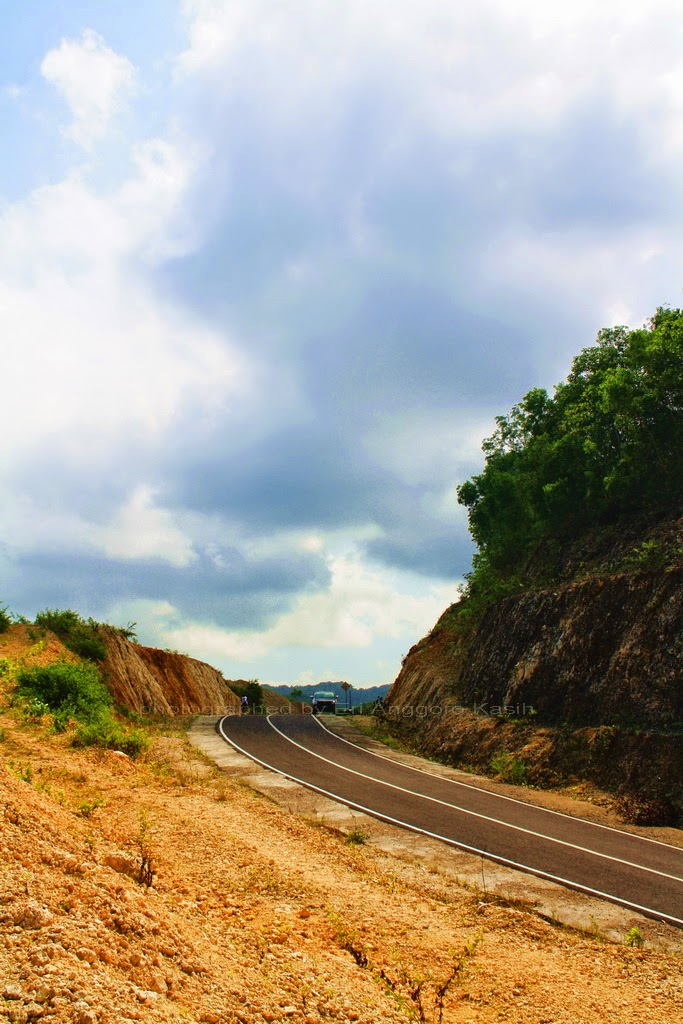 Foto Pantai pinggir jalan membelah bukit kapur