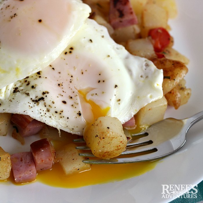Ham Hash by Renee's Kitchen Adventures topped with an egg with the yolk running onto a fork and a piece of potato