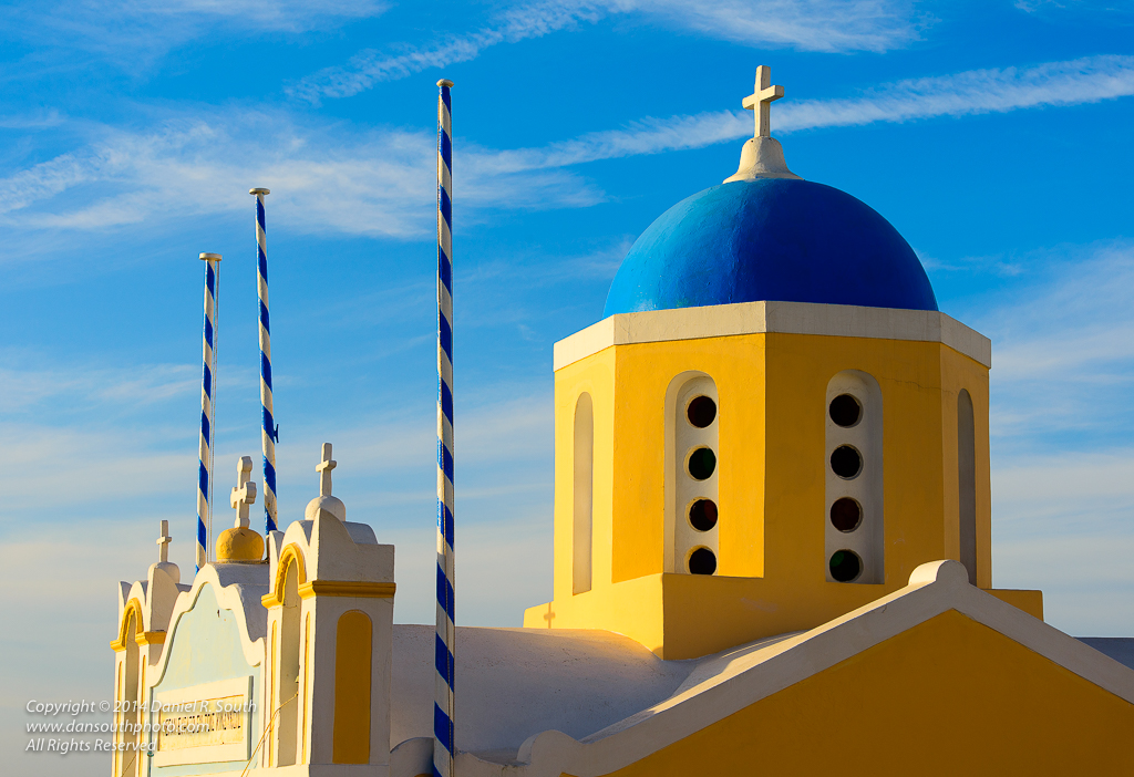 a photo of a golden chapel with a blue dome on santorini greece