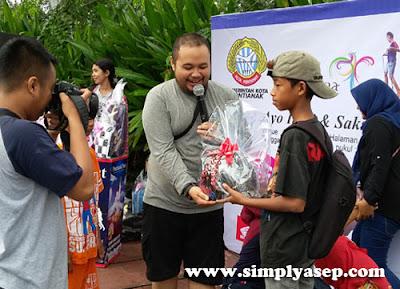 BERHADIAH LANGSUNG :  Bang Bom Bom memberikan bingkisan hadiah kepada para pemenang nya.  Sudah asyik bermain, dapat hadiah pula.  Mau donk.  Foto Asep Haryono/www.simplyasep.com
