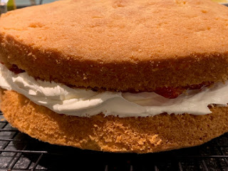 Two sponge cakes sandwiched with whipped cream and jam