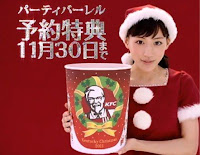 A young Japanese woman in a Santa-style outfit holding a bucket of Kentucky Fried Chicken. There is a red background with white Japanese lettering.
