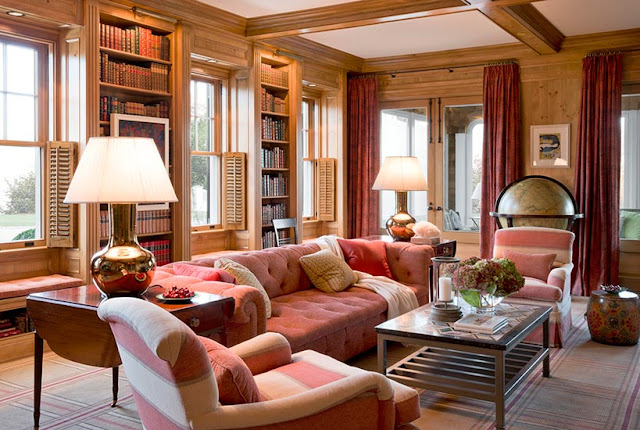 Rose tufted sofas in panelled library den in Meadowmere Southampton home by Carrier and Company