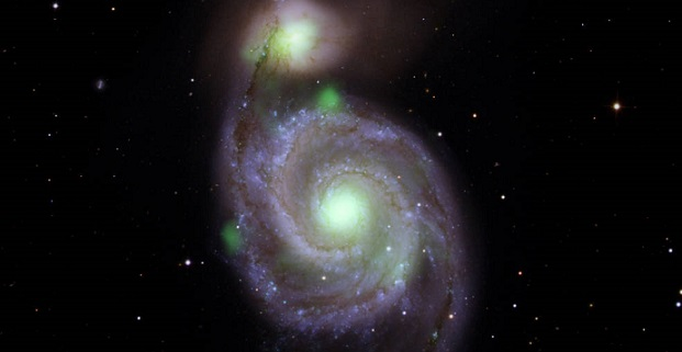 Bright green sources of high-energy X-ray light captured by NASA's NuSTAR mission are overlaid on an optical-light image of the Whirlpool galaxy (in the center of the image) and its companion galaxy, M51b (the bright greenish-white spot above the Whirlpool), taken by the Sloan Digital Sky Survey. Credits: NASA/JPL-Caltech, IPAC