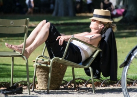 A woman taking a nap at a park.