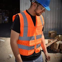 Construction worker in orange safety vest with reflective stripes