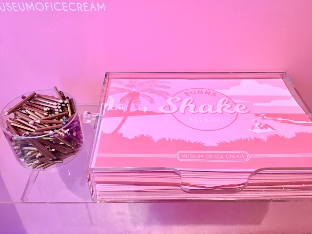 A clear plastic cup filled with mall golden pencils next to a receptacle filled with pink paper placemats