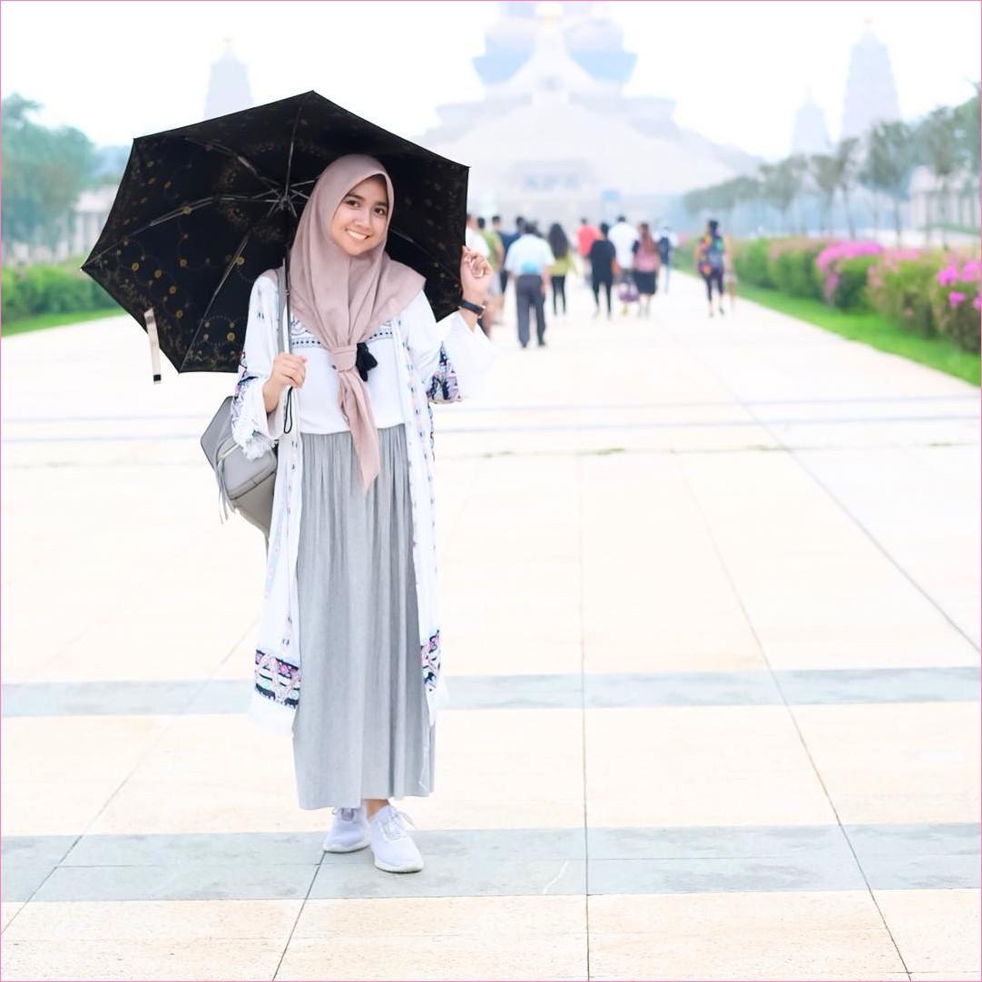 Outfit Rok Untuk Hijabers Ala Selebgram 2018 kets snekares putih kerudung segiempat hijab square krem tua t-shirt outer biru dongker backpack abu sedang broomstick skirt abu payung hitam ootd trendy