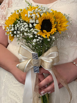 a bride in a lacy dress holding sunflowers, which has a stick of gum in the front.