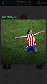 На футбольном поле на колено сел игрок и показывает руками в стороны