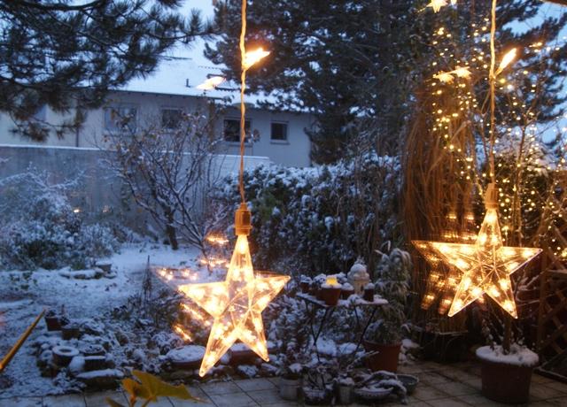 Blick in den Garten mit Schnee zur blauen Stunde