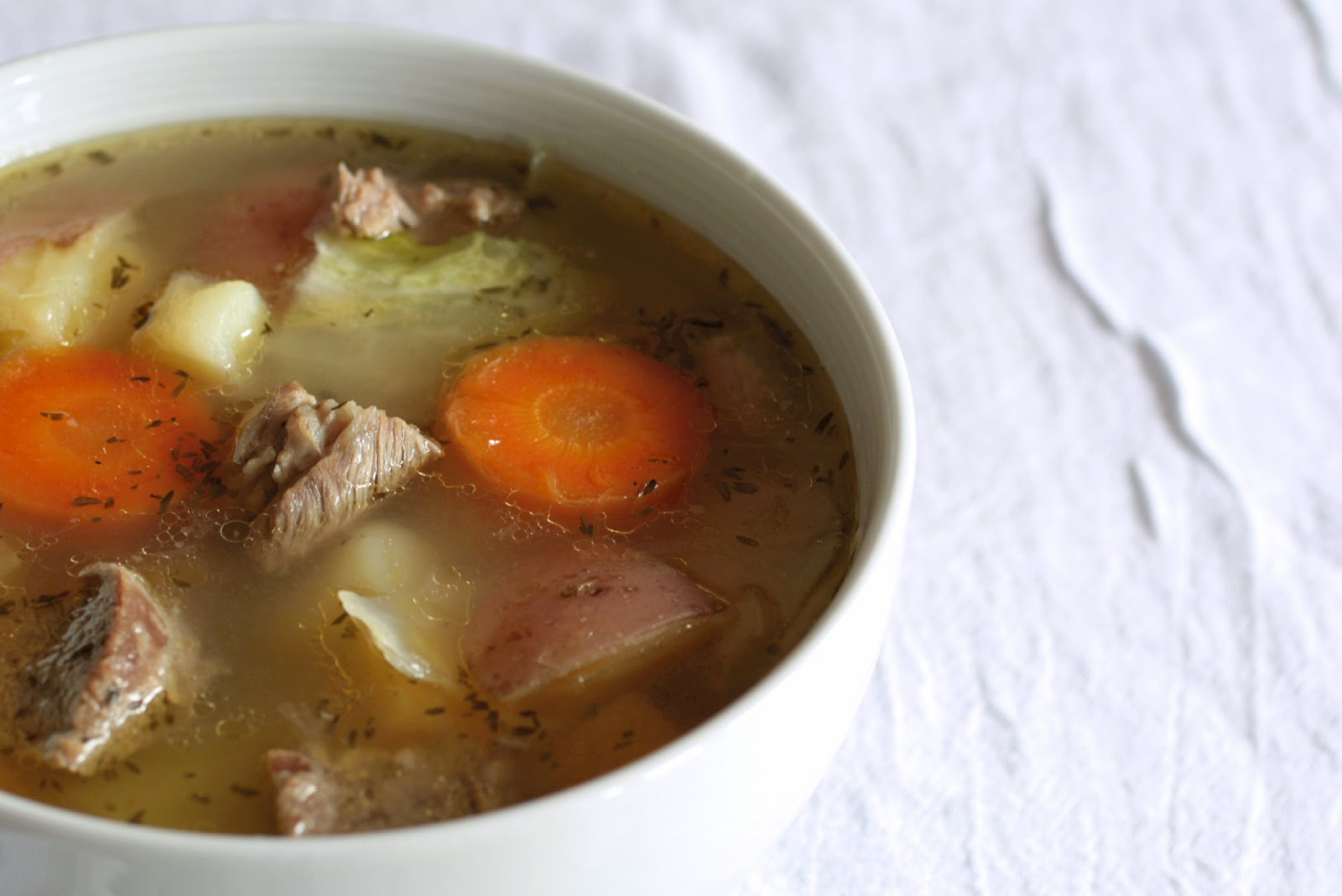 Баранину, морковь и лук выньте из бульона, мясо нарежьте ломтиками и снова положите в бульон.