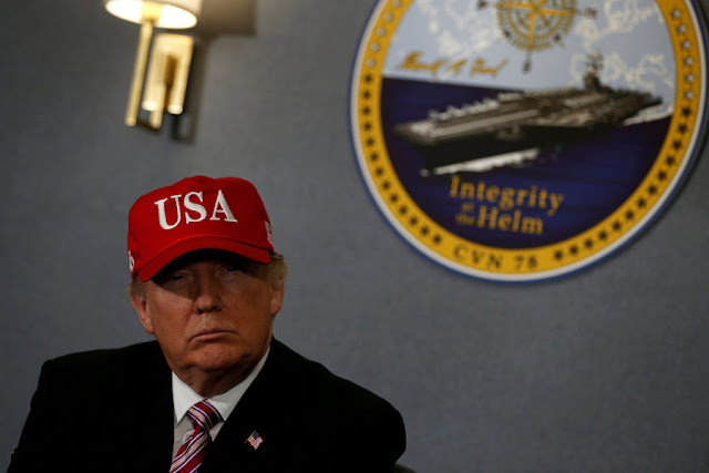 FILE PHOTO: U.S. President Donald Trump gets a briefing before he tours the pre-commissioned U.S. Navy aircraft carrier Gerald R. Ford at Huntington Ingalls Newport News Shipbuilding facilities in Newport News, Virginia, U.S. March 2, 2017. REUTERS/Jonathan Ernst/File Photo