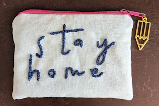 small zip purse with the words stay home embroidered on the front and a pencil charm on the zip
