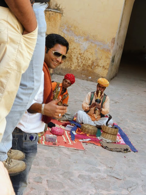 Man giving a thumbs-up with a snake charmer in the background at Amber Fort in Jaipur India