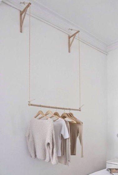 Suspendre une tringle en bois à deux cordes dans la chambre, en voilà une idée facile et pas chère à réaliser pour obtenir un portant suspendu ultra stylé !