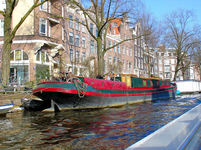 Picturesque house boats like this charming red Amsterdam home line most of the canals, and many of them feature gardens on the top decks!