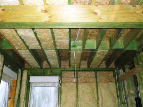 dom drewniany szkieletowy w trakcie budowy - ocieplenie wełną stropu