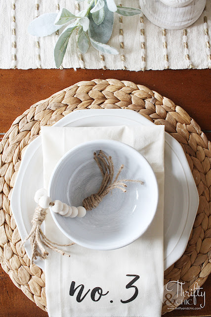 wood bead garland in white bowl with place setting