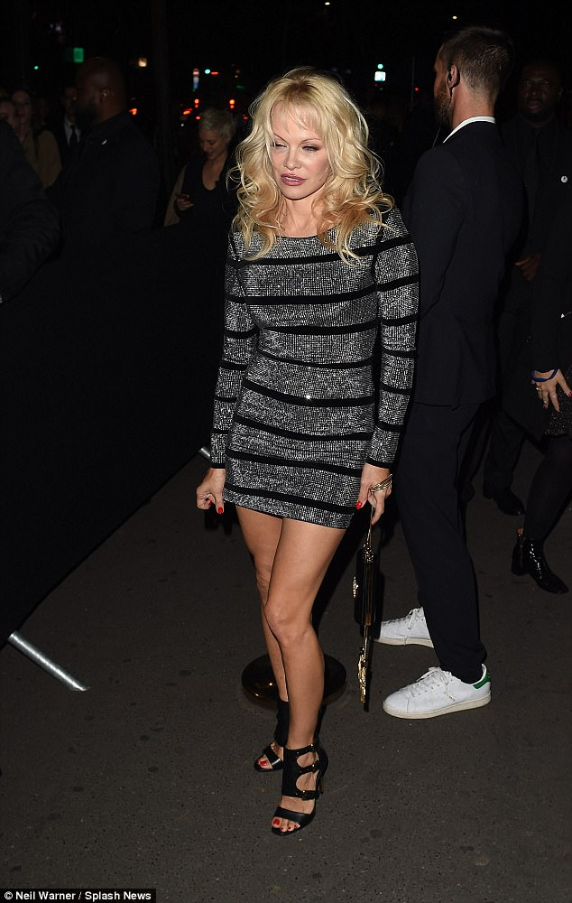 Pamela Anderson trying to pull her dress down in Paris.