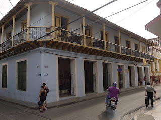 Santiago de Cuba, Calle Heredia, Casa de Estudiante und Casa de Trova. Hellblaues Haus mit riesigen offenen Fenstern zur Strape und umlaufendem Balkon im ersten Stock.