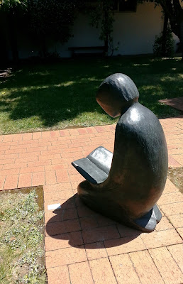 Large statue of a girl reading displayed in a gallery garden.