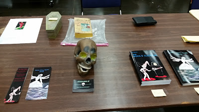 A section of a vendor table displaying books, book marks, business cards and skull prop.