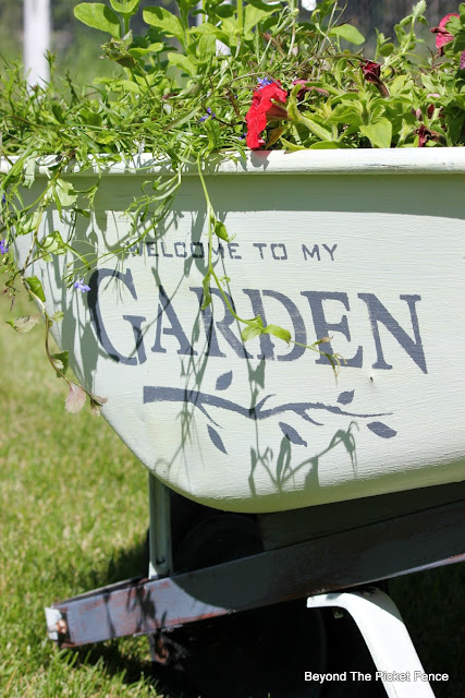 old wheelbarrow, old sign stencils, fusion mineral paint, junky planter, annuals, http://bec4-beyondthepicketfence.blogspot.com/2016/05/welcome-to-my-gardenstencil-paint.html
