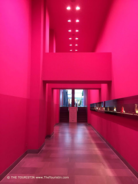 A modern long and high dark pink coloured hallway decorated with ceiling spotlights.