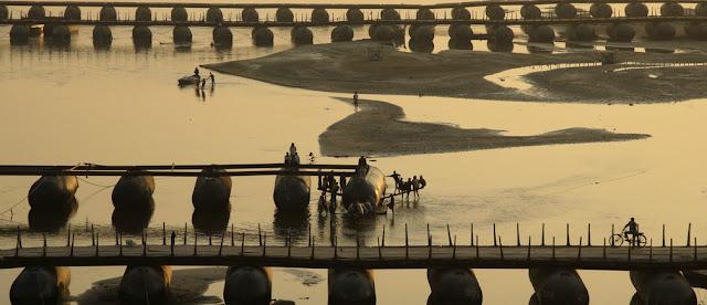 "Labourers work on an under-construction pontoon bridge spanning the river Ganga ahead of the ""Kumbh Mela""."
