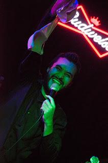 fotografía de concierto de un cantante sosteniendo un brasiere que le aventaron durante su presentación