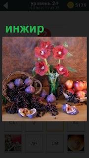 Стоит ваза с красными цветами и лежит корзина, внутри которой находится инжир, который выпадает на поверхность стола