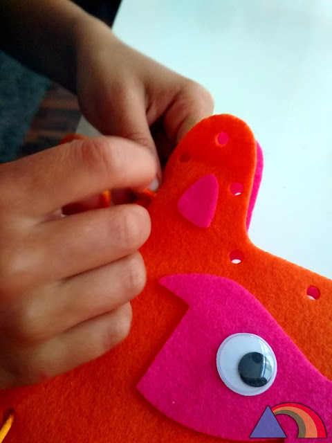 Niño pasando cordón por agujeros hechos en dos piezas de fieltro para unirlas.