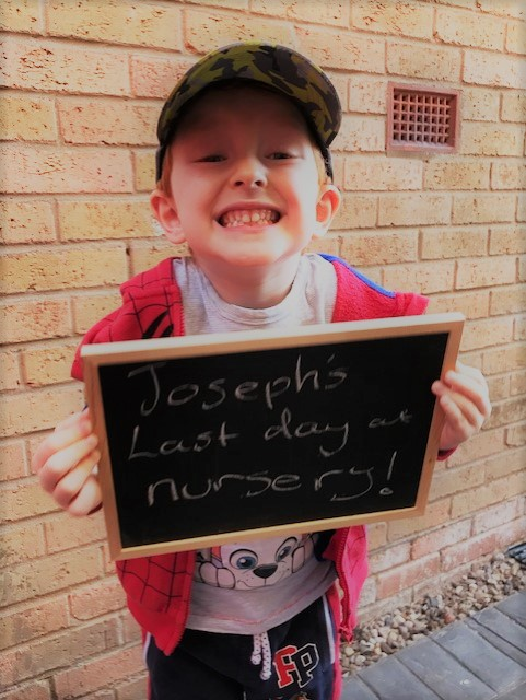 Little boy holding a chalk board that reads 'Joseph's last day at nursery'