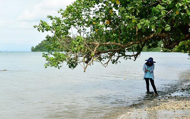 Seorang wisatawan sedang asyik mengabadikan di tepian pantai