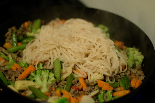 The rice noodles being added to the pan with the ground beef and the vegetables on the stove.
