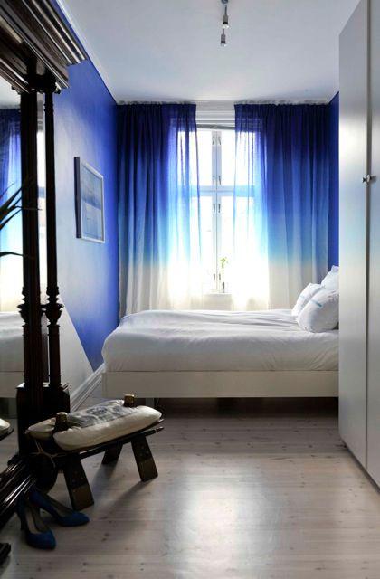 Quarto de casal decorado com cortina com tingimento ombré, paredes azuis, roupa de cama clara