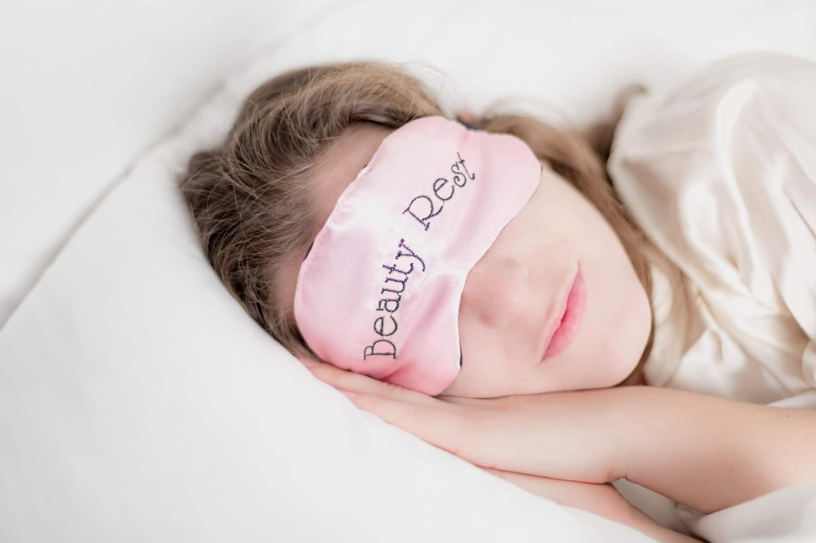 "A woman rests her head on a pillow and wears a pink satin mask that states: ""Beauty Rest"", allowing her to catch a little extra sleep."