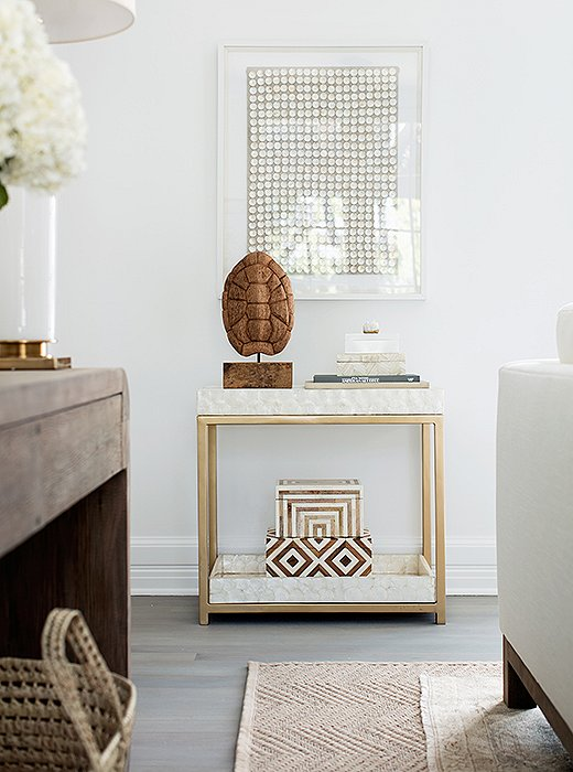 """Inspiring interior design in a modern living room. The bar cart is covered in capiz—part of the mission to add rich texture everywhere. """"There's no real color here,"""" Alex says, """"but the capiz makes the whole spot dynamic."""" And by tucking the shell and books below, Erin and Gabe can easily turn the spot into a setup for drinks when they entertain."""