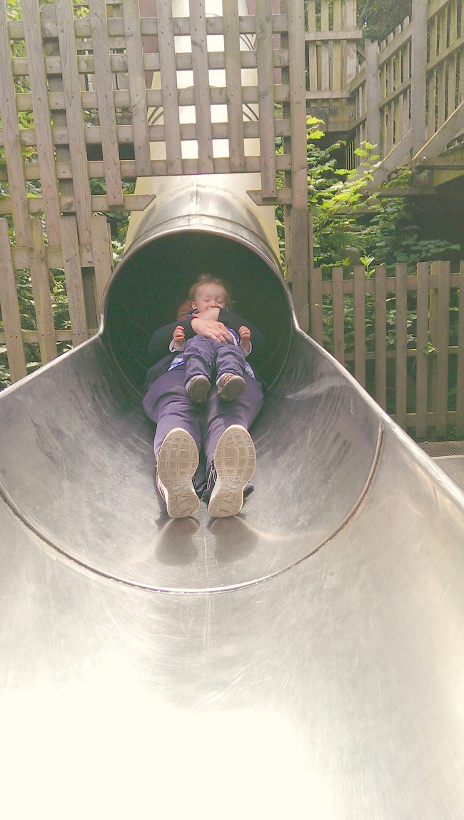 woman-and-toddler-emerging-from-slide-at--Perrygrove-Railway-adventure-playground