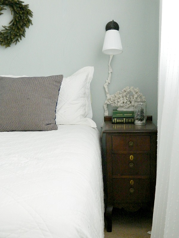 light blue-gray bedroom with white bedding quilt and antique stained furniture