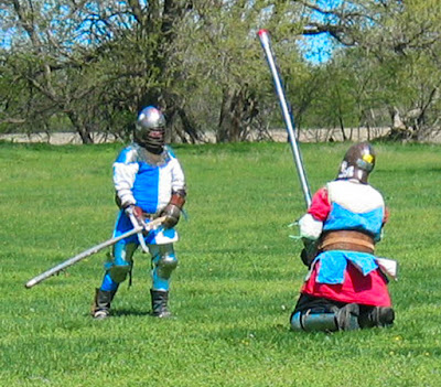 Two medieval style fighters, one standing, one on his knees, weapons in hand, fighting.