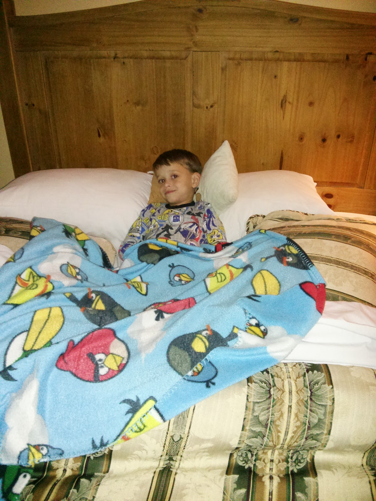 the little man in bed with his angry birds blanket on OneQuarterMama.ca copyright 2014