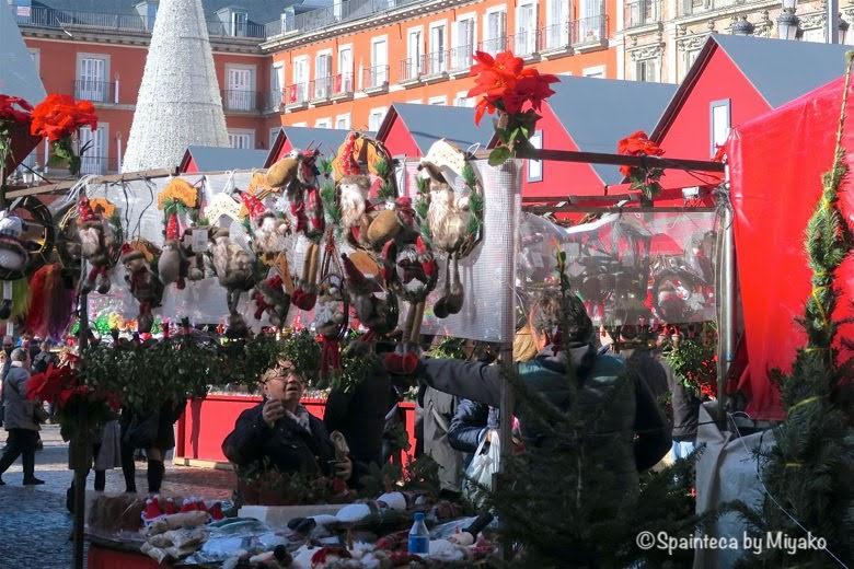 マドリードのマヨール広場でクリスマス用のお飾りを買い求める女性`