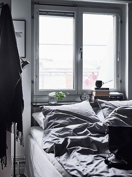 décoration draps de lit gris dans une chambre blanche et noire